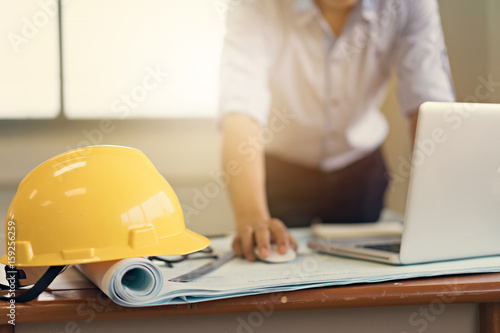 Engineer man working with laptop and blueprints sketching a construction project .Business concept with vintage color.
