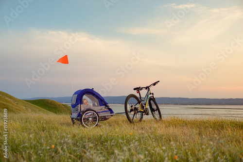 Biking in the hills at sunset with child trailer Poster