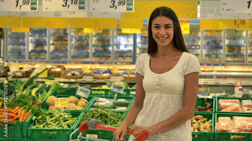 Keuken foto achterwand Boodschappen A beautiful young girl (woman) at the grocery store, in a white tank top, supermarket, chooses alcoholic drinks products, with a cart. Concept: buy products, large purchases, market, store, products.