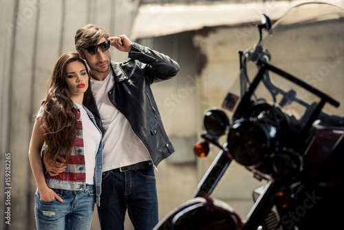 Foto op Canvas Scooter Stylish young couple standing embracing and looking at motorbike
