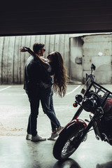 Stylish young couple in love hugging while standing in garage with motorbike