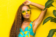 Close-up of a beautiful young pretty girl on a yellow wall, in a turquoise overall with a print of bananas, leaves of a tropical plant, fashionable bright look, tanned bronze skin, summer vacation