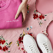 Hands Arranging Flat Lay Shot Of Female Holiday Clothing