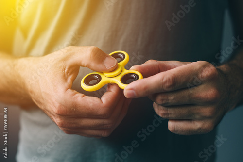Yellow fidget spinner in male hand