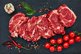 Fresh raw beef steaks with pepper and tomatoes on black slate board. Copy space, top view.