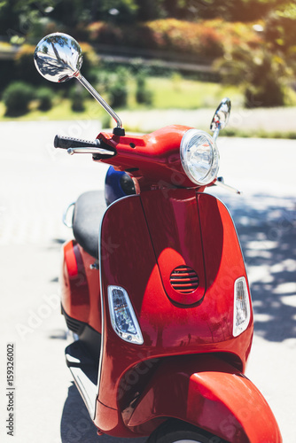 Close up red color vintage scooter in city summer street, hipster motorcycle on urban background, transport bike for tourism and travel adventure, holiday concept