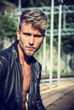 Attractive blond young man standing on railroad tracks, wearing only black leather jacket, looking at camera