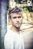 Attractive blond young man standing on railroad tracks, wearing white t-shirt, looking away