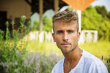 Attractive blond young man standing in front of old porch, wearing white t-shirt, looking at camera