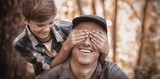 Boy covering fathers eyes in forest - 159350421