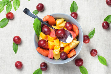Mixed fruit salad in the blue bowl. Healthy sliced fresh fruits on a linen grey background. Red berries, green leaves and spoon on table © romanovad