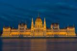 beleuchtetes Parlamentsgebäude in Budapest mit Donau im Vordergrund