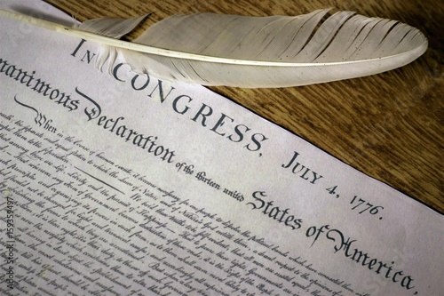 Poster Declaration of Independence with feather quill on wood surface