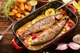 Baked fish with lemon sauce and vegetables in a pan - 159360233