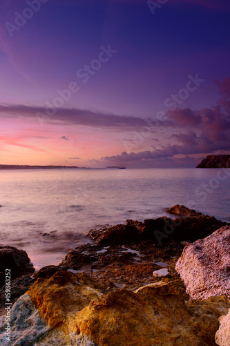 Beautiful colorful sunrise at the sea with dramatic clouds and boulders. Beauty world natural outdoors travel background