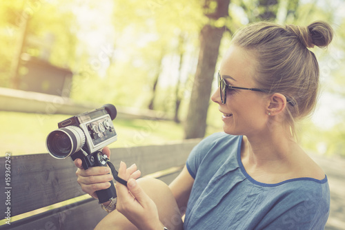 Poster Summer. Young beautiful woman with vintage camera