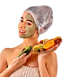 Avocado clay face mask. Woman in medical hat holding half of green fruit isolated background. Facial beautiful procedure concept. Masks for skin created from natural ingredient.