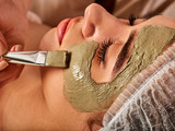 Mud facial mask of woman in spa salon. Massage with clay full face. Girl on with therapy room. Beautician with brush therapeutic procedure . Unique properties of therapeutic clay .