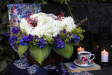 Wicker basket with white hydrangea, blue delphinium, cuff, leaves, hosts in the summer garden. A cup of tea, candles in garden lanterns. Flower composition.