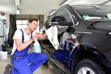 Fahrzeugaufbereitung: professionelle Autoreinigung in einer Waschanlage - Mann poliert Lack eines Autos //