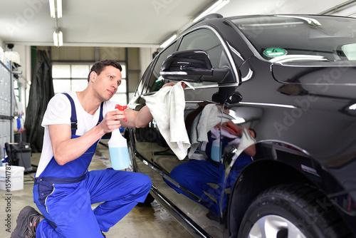 Fahrzeugaufbereitung: professionelle Autoreinigung in einer Waschanlage - Mann poliert Lack eines Autos  // - 159417876