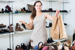 cheerful brunette with bags in footwear shop