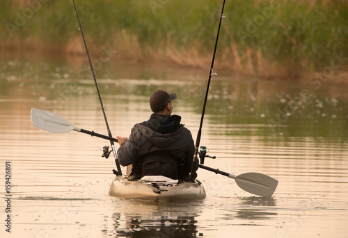 Poster Fisherman in inflatable canoe.