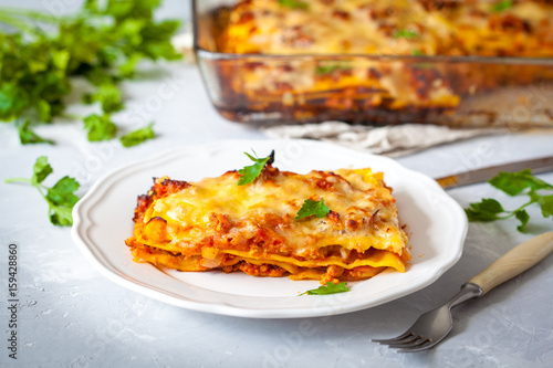 Piece of traditional Italian meat lasagna on a white plate. - 159428860