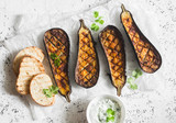 Grilled eggplant and sauce tzatziki on a light background, top view. Baked aubergine - 159430651