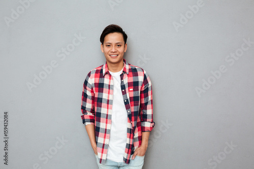 Poster Smiling asian man standing over grey wall.