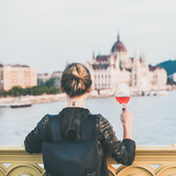 Young woman tourist standing with glass of rose wine at Margaret bridge in Budapest, Hungarian Parliament building and Duna river at background, square crop