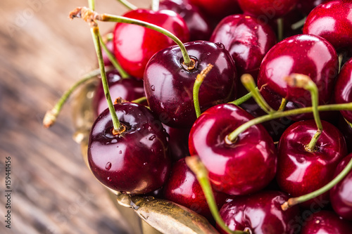 Fotobehang Kersen Cherries. Fresh sweet cherries. Delicious cherries with water drops in retro bowl on old oak table.
