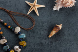 Travel memories - starfish, screw shell and necklace on grayish ground