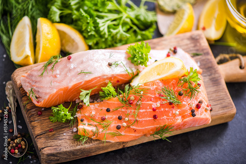 Salmon fish raw fillets on board with herbs