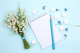 A bouquet of lilies of the valley, a notepad and a pencil lie on a blue wooden table