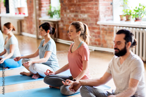 group of people making yoga exercises at studio - 159472423
