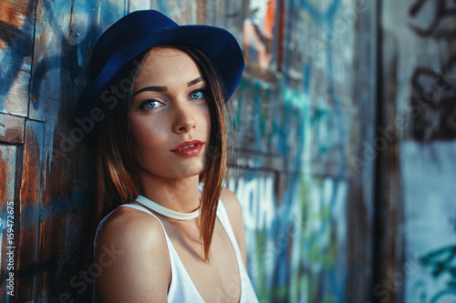 Portrait of a young attractive woman with blue eyes and hat
