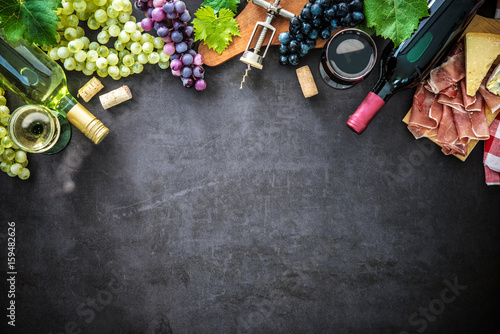 Wine bottles with grapes, cheese, ham and corks