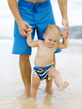 Son (12-17 months) learning to walk with father on beach - 159497237