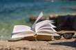 Reading open book at beach near the sea during summer vacation