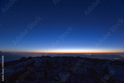 Stunning view of the night sky and a rock near the summit of Westliche Karwendelspitze facing the flat land shortly after sunset Poster