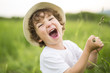 Portrait of adorable kid boy with hat standing on a summer meadow