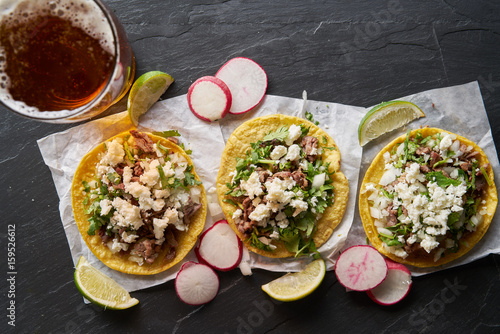 beer and carne asada mexican tacos with queso fresco cheese shot in top down composition