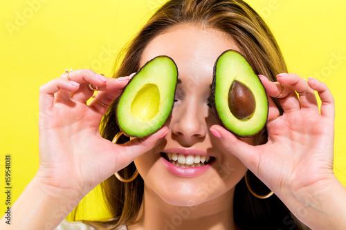 Happy young woman holding avocado halves