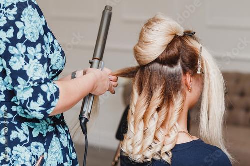 Woman hairdresser making hairstyle in beauty salon using iron curler Slika na platnu