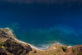 Green Madeira coast with azure water and blue sky