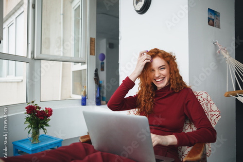 Portrait of a pretty redheaded woman working on laptop