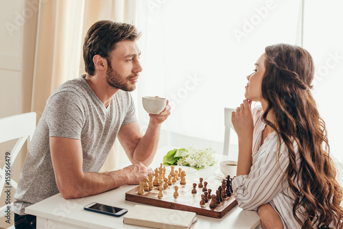 young couple playing chess and talking while drinking coffee at home плакат