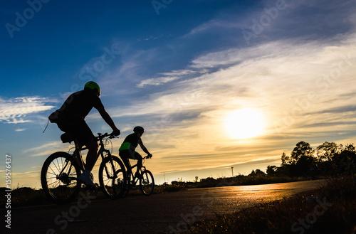 Sylwetka cykliści jedzie rowery na drodze przy zmierzchem.