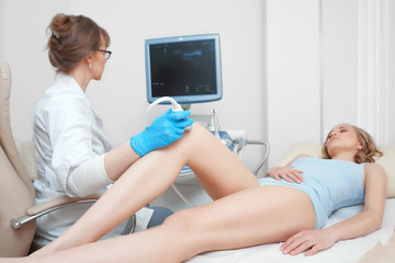 Female doctor working at the clinic using ultrasound scanning machine examining injured knee of her female patient lifestyle healthcare medicine hospital professionalism occupation.